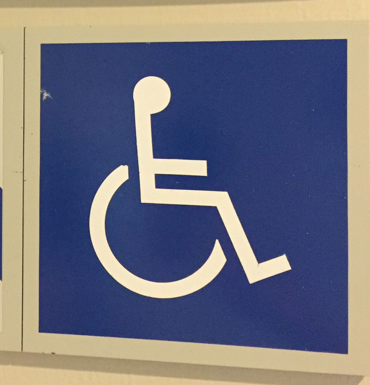 In this logo, the main focus, the handicapped sign, is the