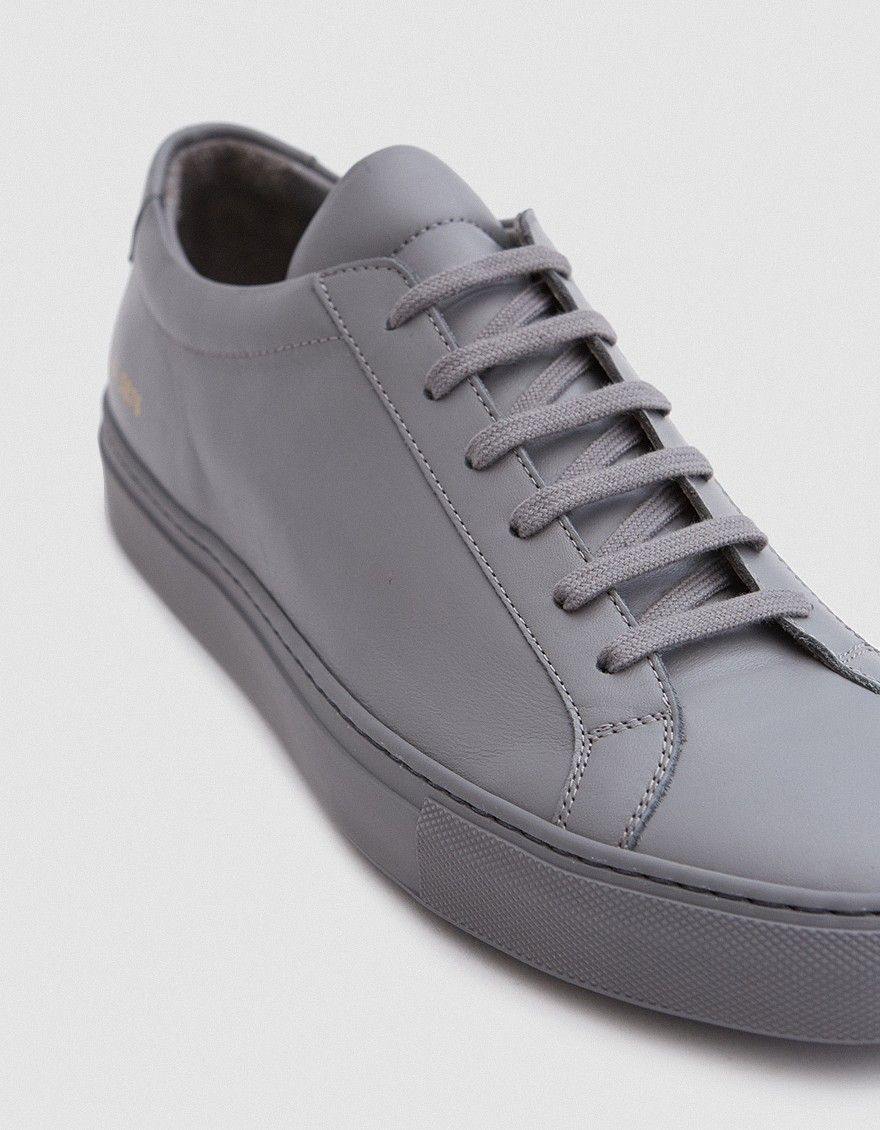 84180d19ba5a Low top sneaker from Common Projects in Medium Grey. Lace-up front with  flat laces. Lightly padded tongue and collar. Leather lining.