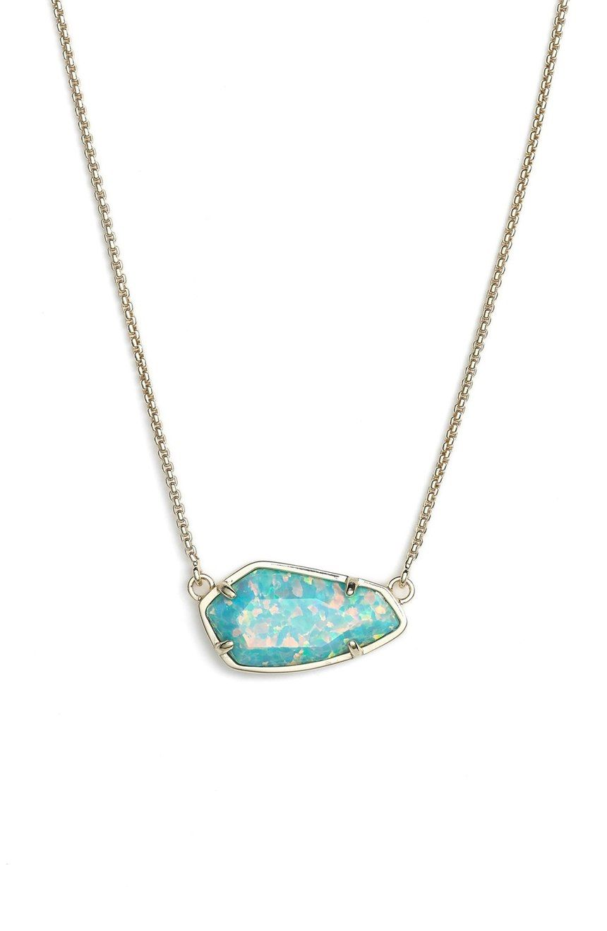 A luminescent stone set in a modern geoinspired pendant centers