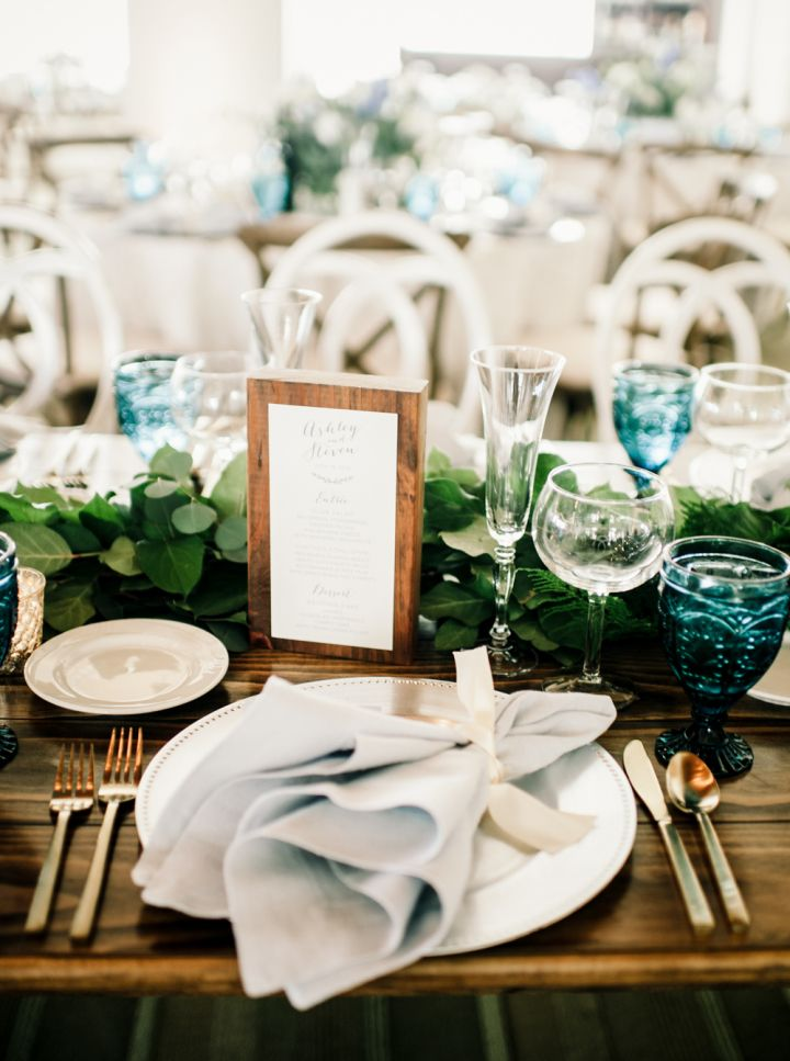 Beautiful wedding table decoration + greenery + blue vintage glassware #bluewedding #weddingdetails