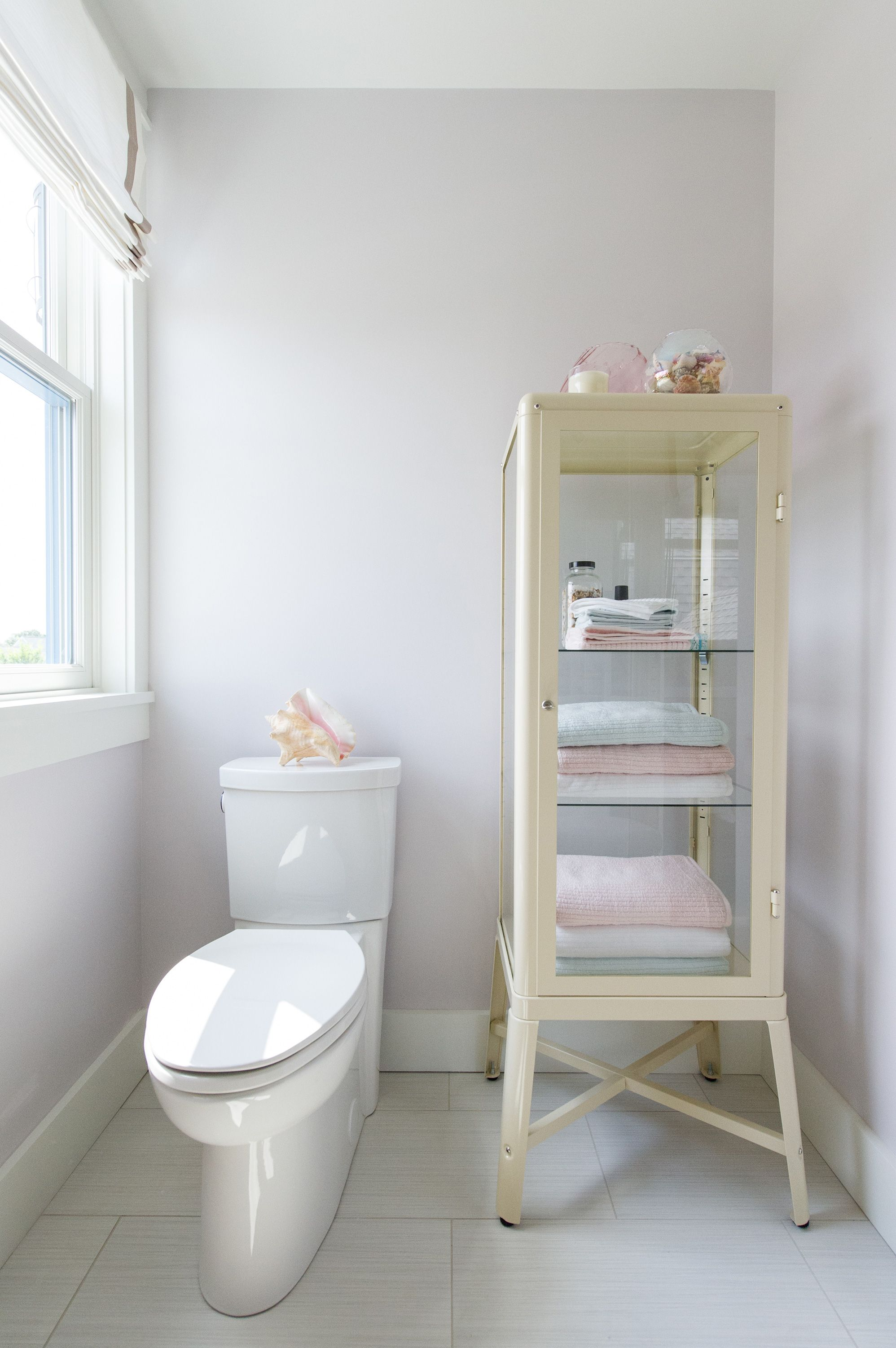 A retro glass cabinet by IKEA handily houses extra towels and bath accessories Clean ActiVate