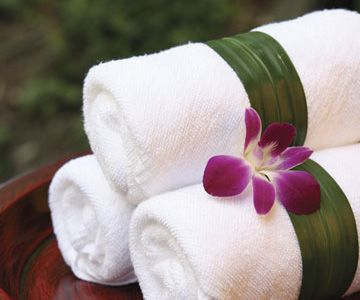 Clean white towels wrapped in ti leaf orchids