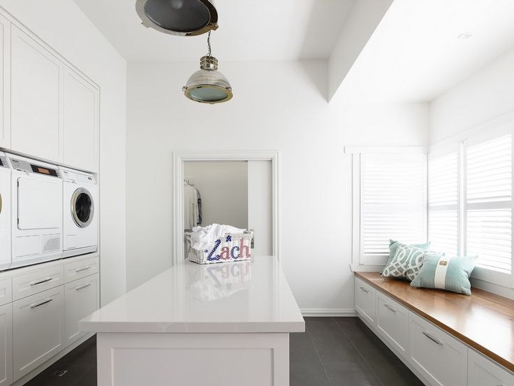 Large Laundry Room Boasts Washer And Dryer Stacked Between White