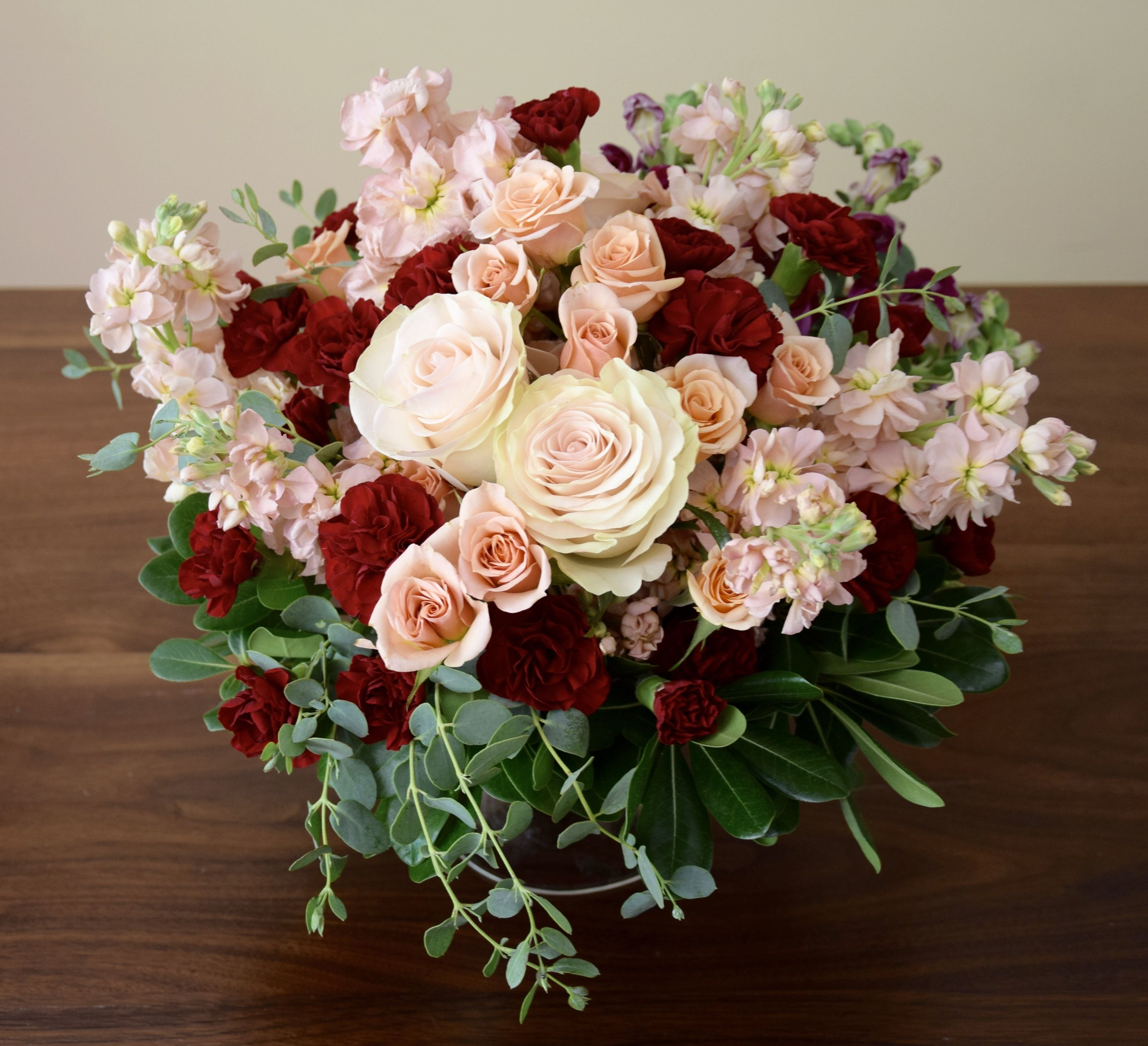 Wedding Table Flower Centerpiece With An Accent On Burgundy And Peach Colors Roses Carnation Wedding Centerpieces Carnation Centerpieces Wedding Table Flowers