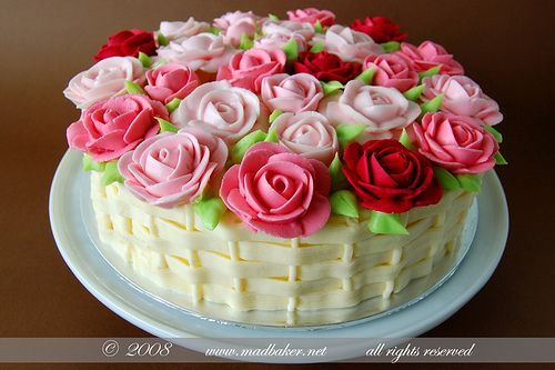 Mad about a Basket of Roses cake- this fantastic, gorgeous cake is topped with piped royal icing roses. The cake itself is victorian sponge with raspberry preserve, fresh raspberries and buttercream icing in the center, and covered with vanilla buttercream, and a piped basket weave on the sides in buttercream. Absolutely gorgeous!