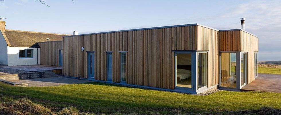 A flat roof longhouse clad in vertical larch boarding for Flat roof bungalow designs