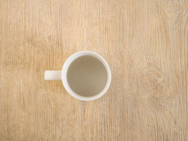 an isolated empty coffee cup on a wood deck