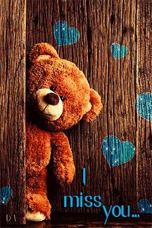 Плюшевый мишка стоит на деревянном фоне с голубыми сердечками (I miss you / Я скучаю по тебе)