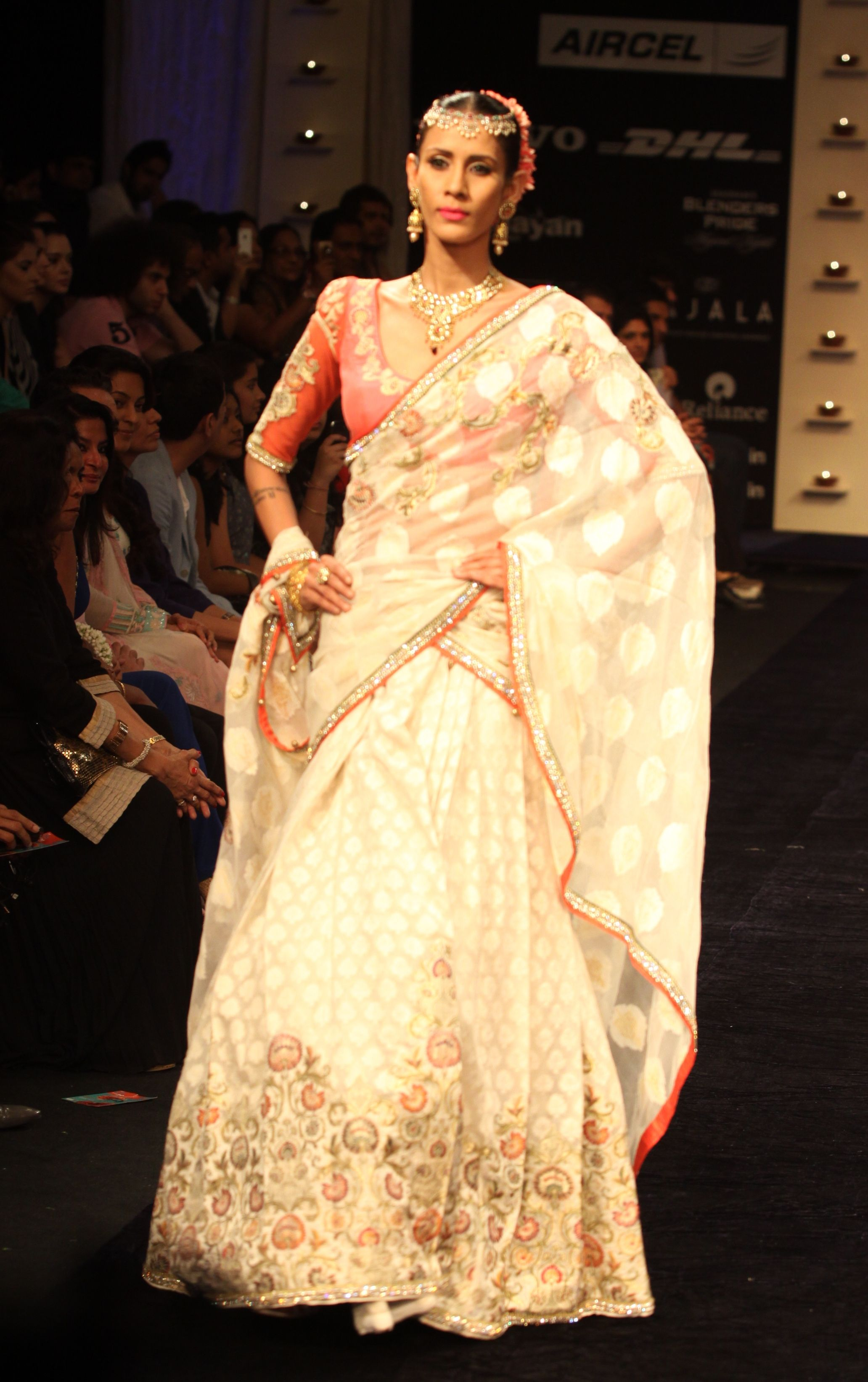 Ivory lehenga with a coral embroidered blouse with an ivory dupatta