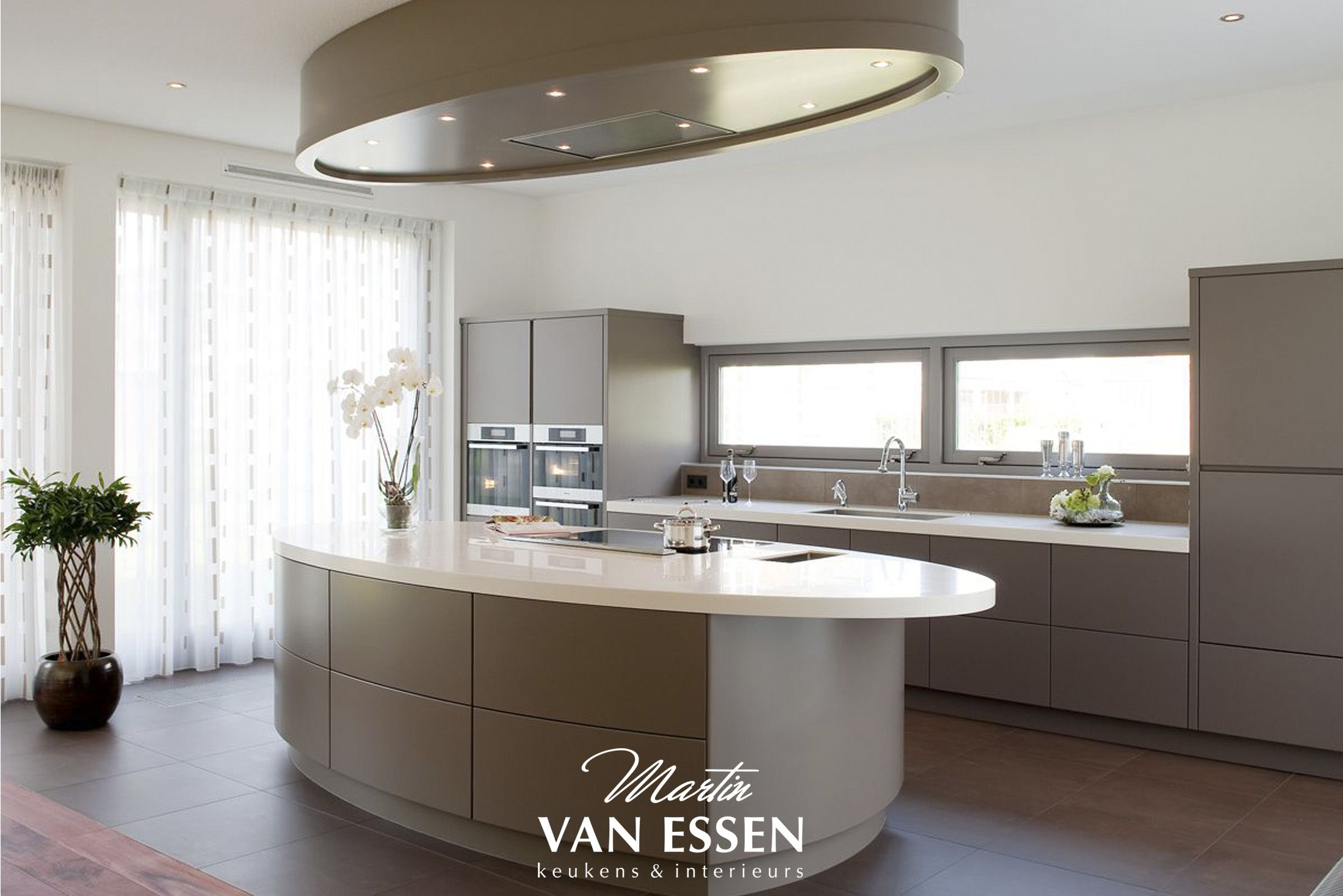 Een prachtige grijze keuken. modern met uniek kookeiland. helemaal