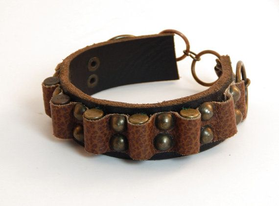 "Whether you call it a ""bandoleer"", or ""bandolier"", or just the best darned accessory for doomsday, this riveted leather bracelet is perfect for any wasteland gunslinger. The rustic, unique design incorporates recycled materials, including 6 .22 caliber brass bullet casings and re-purposed hardware, and uses an over sized spring ring clasp for ease of use."