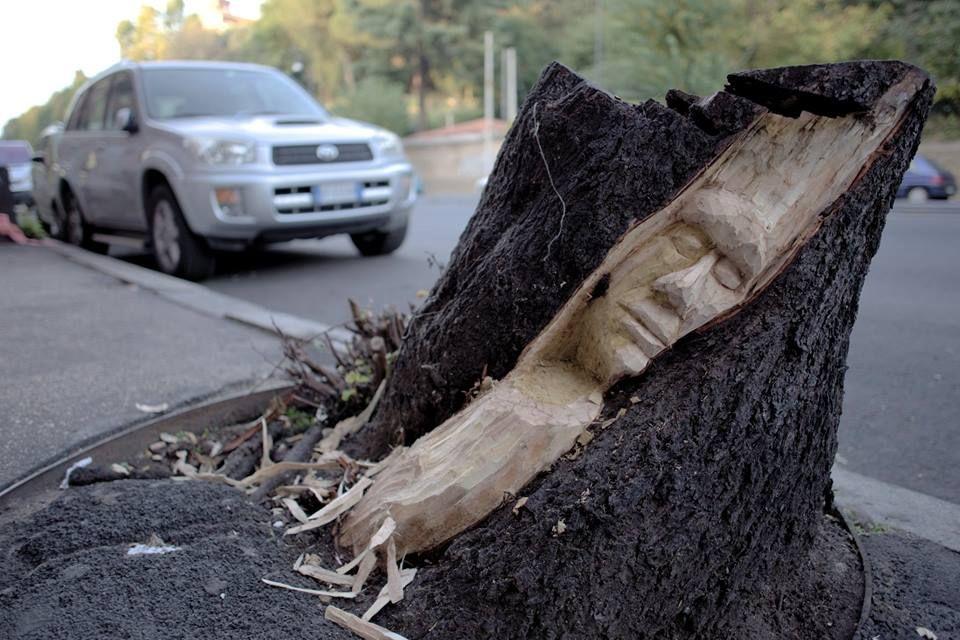 Chi vive a Roma avrà notato quanti tronchi mozzi di alberi morti adornano tristemente le vie della città. Agli occhi più attenti non sarà sfuggito che negli ultimi mesi alcuni di questi tronchi hanno preso vita, assumendo volti ed espressioni …