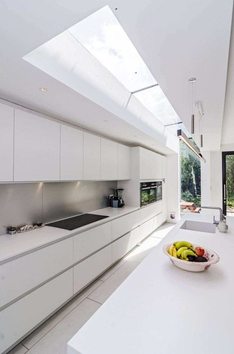 White minimal modern handleless kitchen. Pronorm Y-Line, Corian, Siemens. London Victorian side return conversion. #whitegalleykitchens