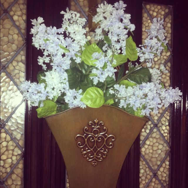 Front door bucket with artificial lilacs for springtime