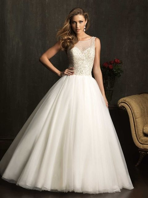 Allure Bridals Style: 9050 This elegant ball gown features a sheer-illusion neckline that continues to a V-shaped back. The sleeveless bodice is beautifully encrusted with Swarovski crystals and tiny pearls.  Colors: White/Silver, Ivory/Silver, Champagne/Silver Fabric: English Net Sizes: 2 - 32