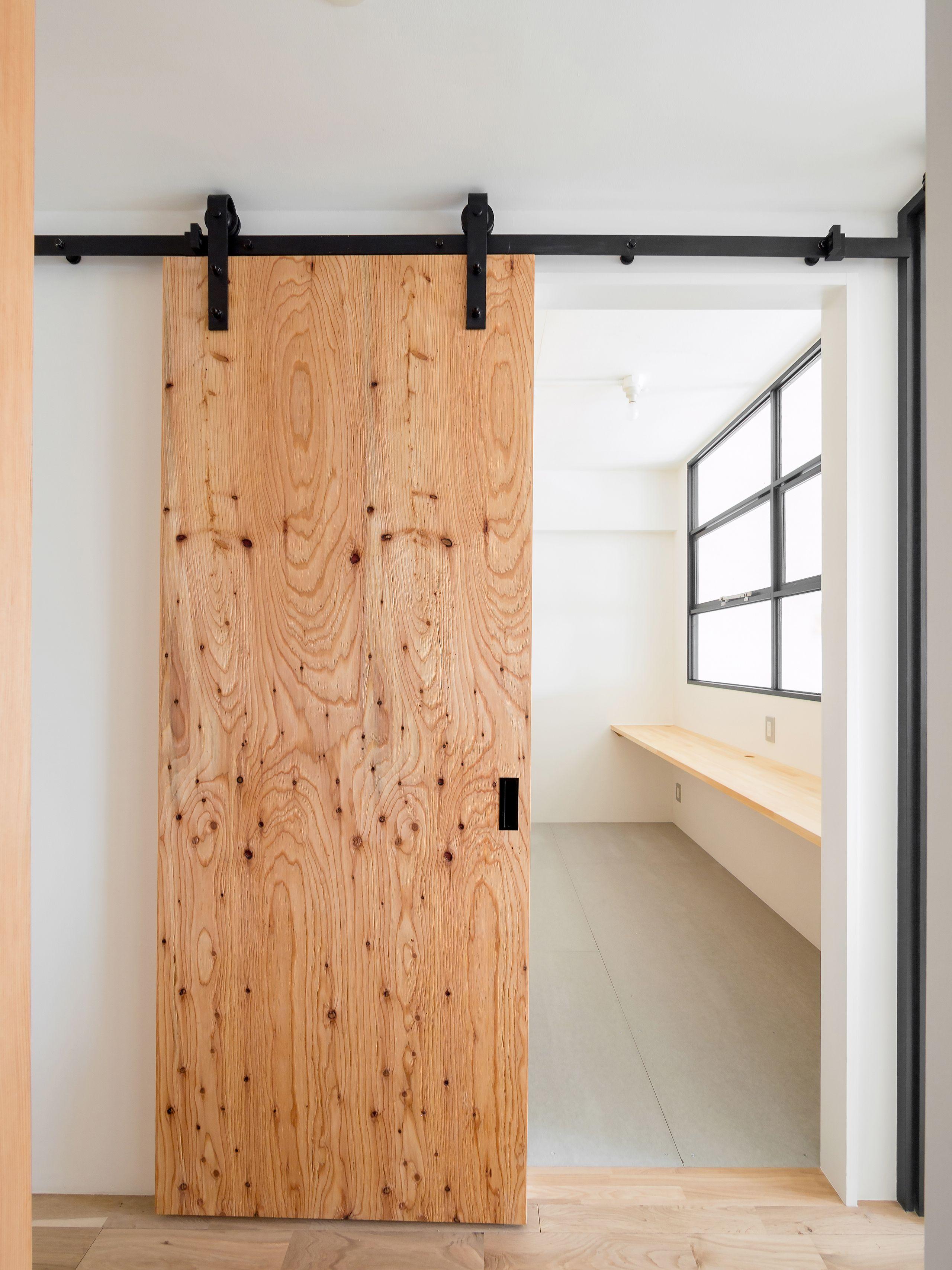 木とモノトーンの調和した家 ラーチ合板で仕上げたバーンドア ドア 建具 引き戸 レール ドアリフォーム 引き戸 レール 引き戸