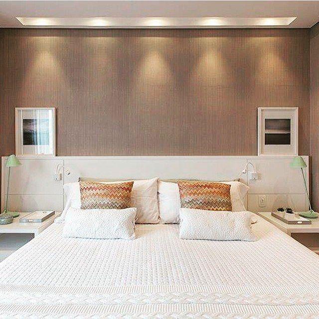 Quarto, destaque para o papel de parede imitando linho e iluminação valorizan