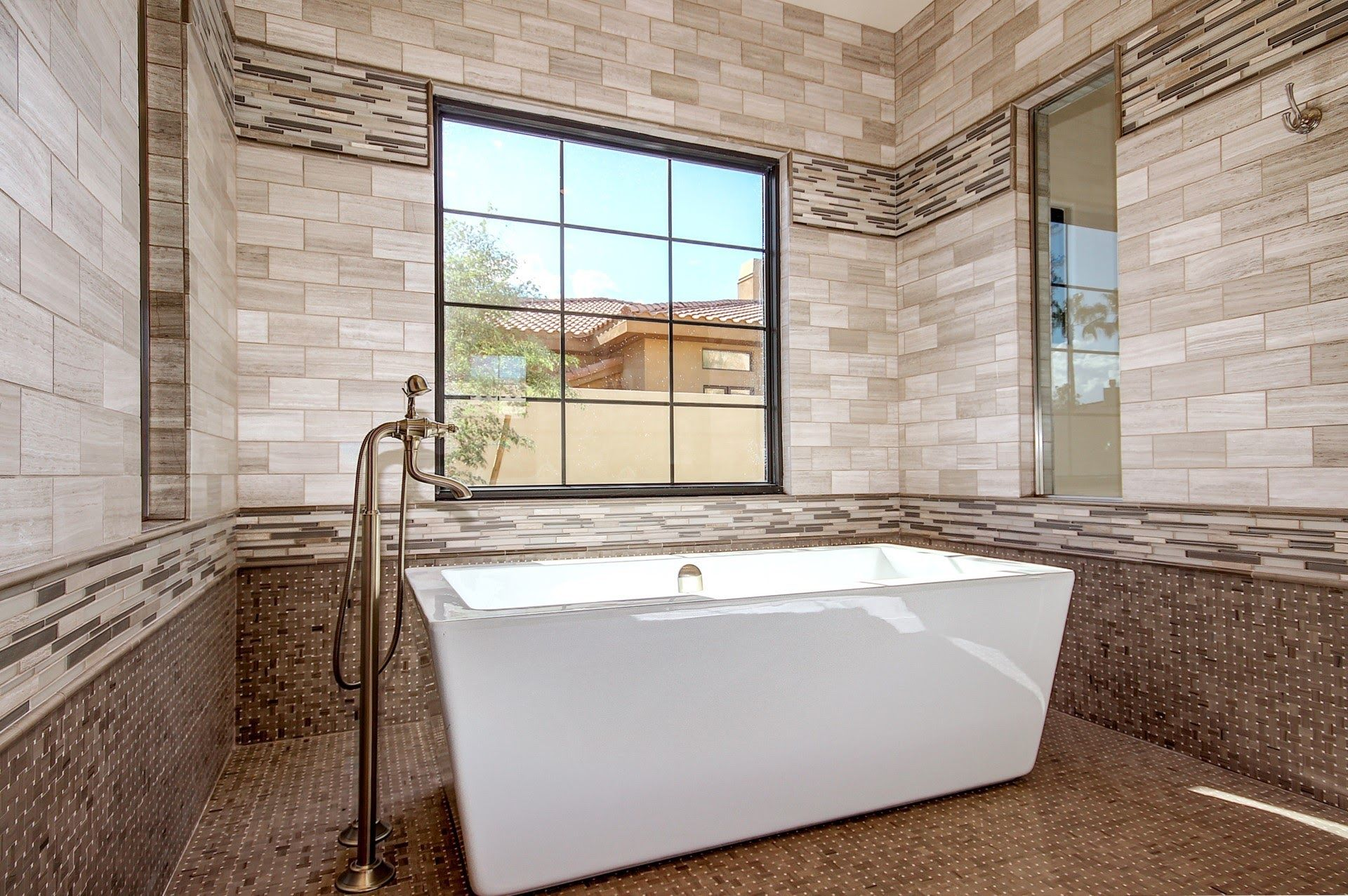 Large soaking tub surrounded by grey limestone and mosaic glass tile ...