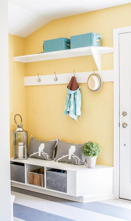Yellow and blue mudroom features walls painted bright yellow lined with a shelf lined with blue bins and a row of hooks over a built-in bench filled with galvanized steel bins and gray pillows alongside a gray striped floor. #graystripedwalls
