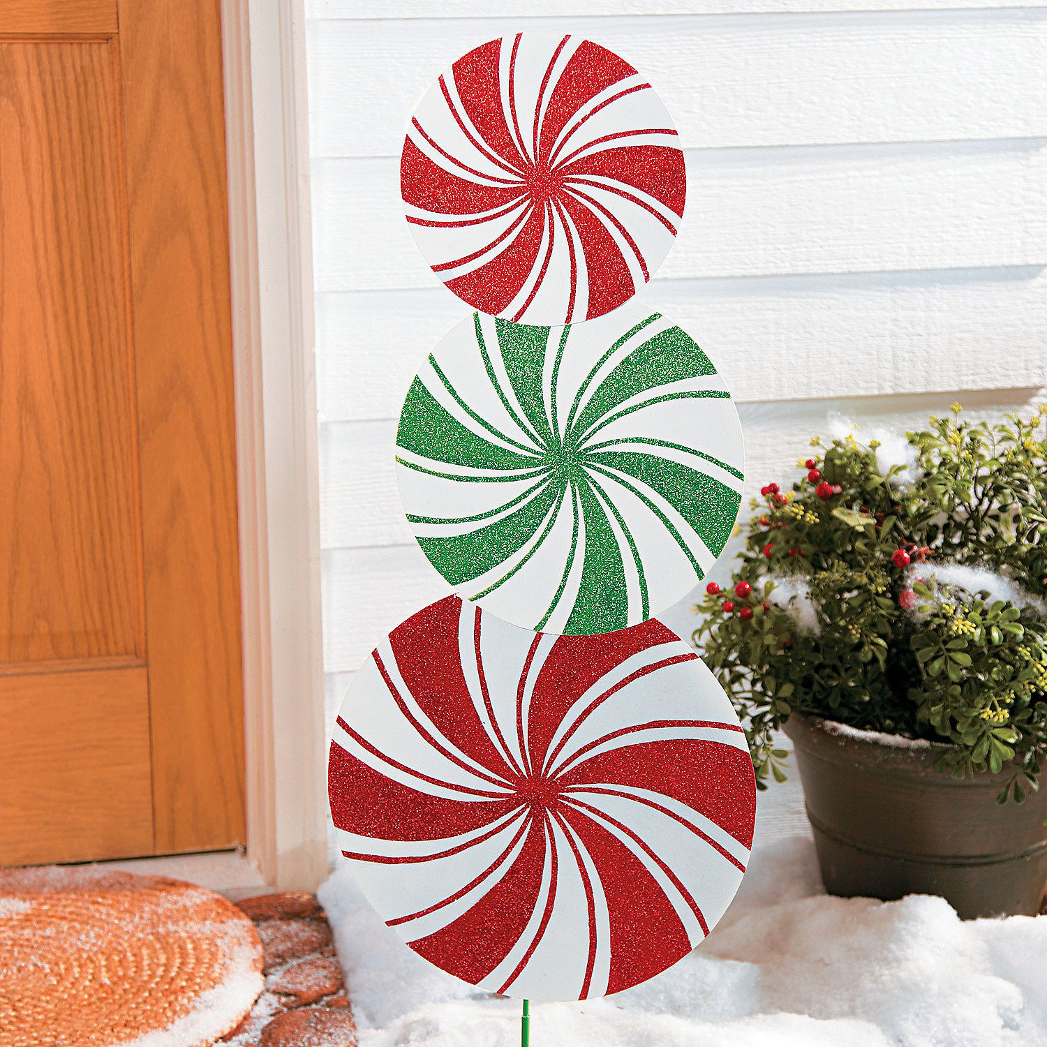 "A sweet way to greet friends and family during the holidays, this glittery yard art adds a pop of color to your outdoor Christmas decorations. Metal. Simple assembly required. Stakes, 7 1/4""; peppermints, 28 3/4"" x 13"" © OTC"