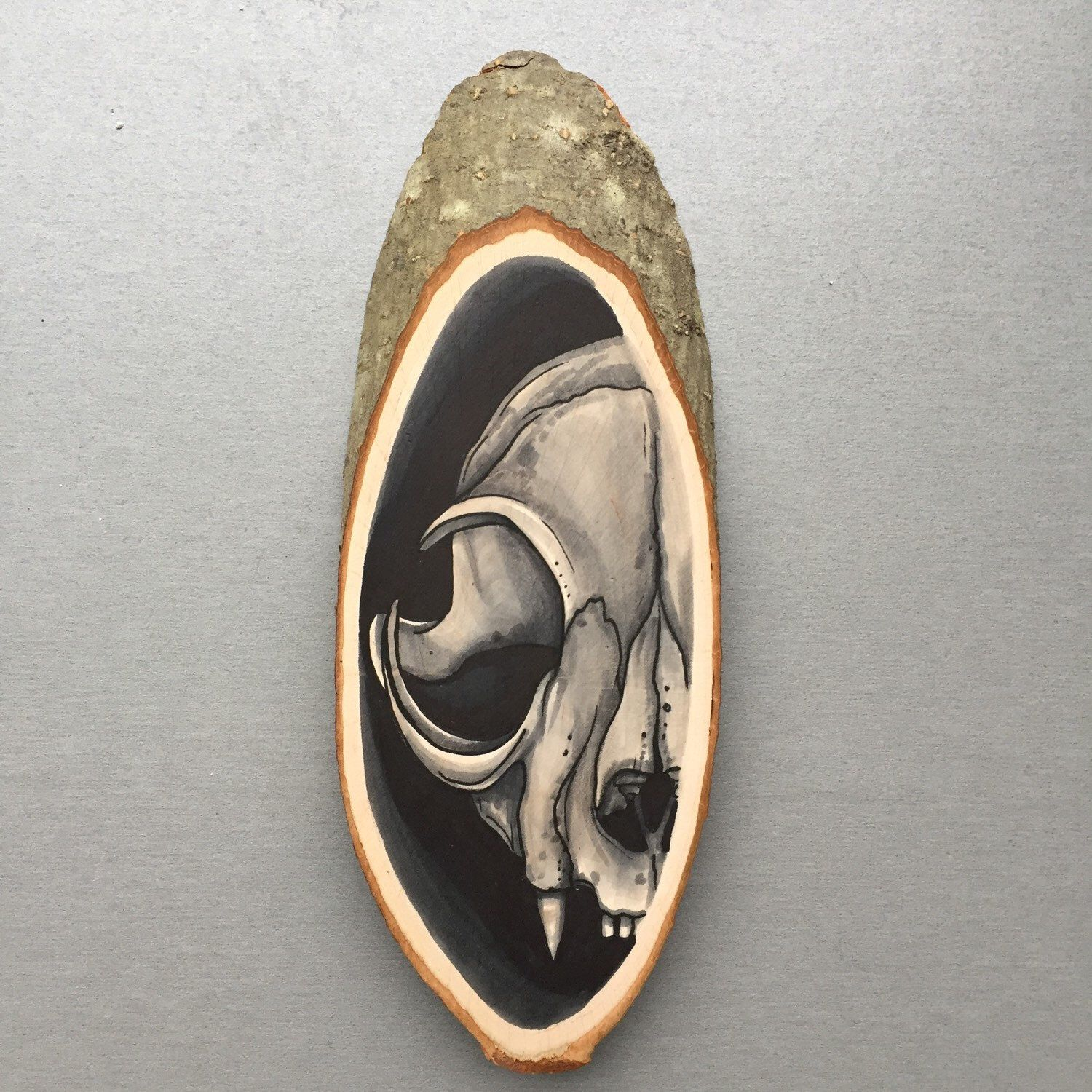 Wood slice with an original drawing of a feline cat skull wall
