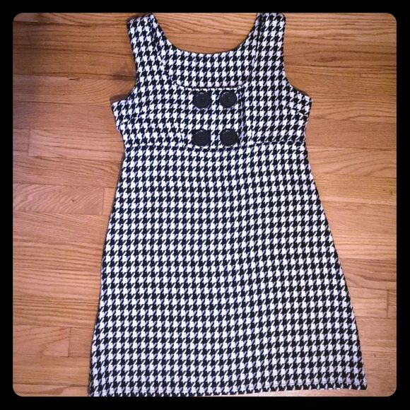 Sleeveless houndstooth dress This is a very cute jumper style houndstooth dress with oversized buttons in front. The material is thicker and heavier so this dress is great for fall and winter. Dress has no tag but fits a size medium, doesn't have much stretch in the bust area. Dresses