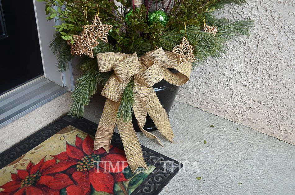 Starry Christmas Arrangement With Birch Logs ~ This outdoor arrangement will look fabulous on an outdoor porch. It is simply made with Christmas greenery, birch logs and gold grapevine stars to give it a special touch!