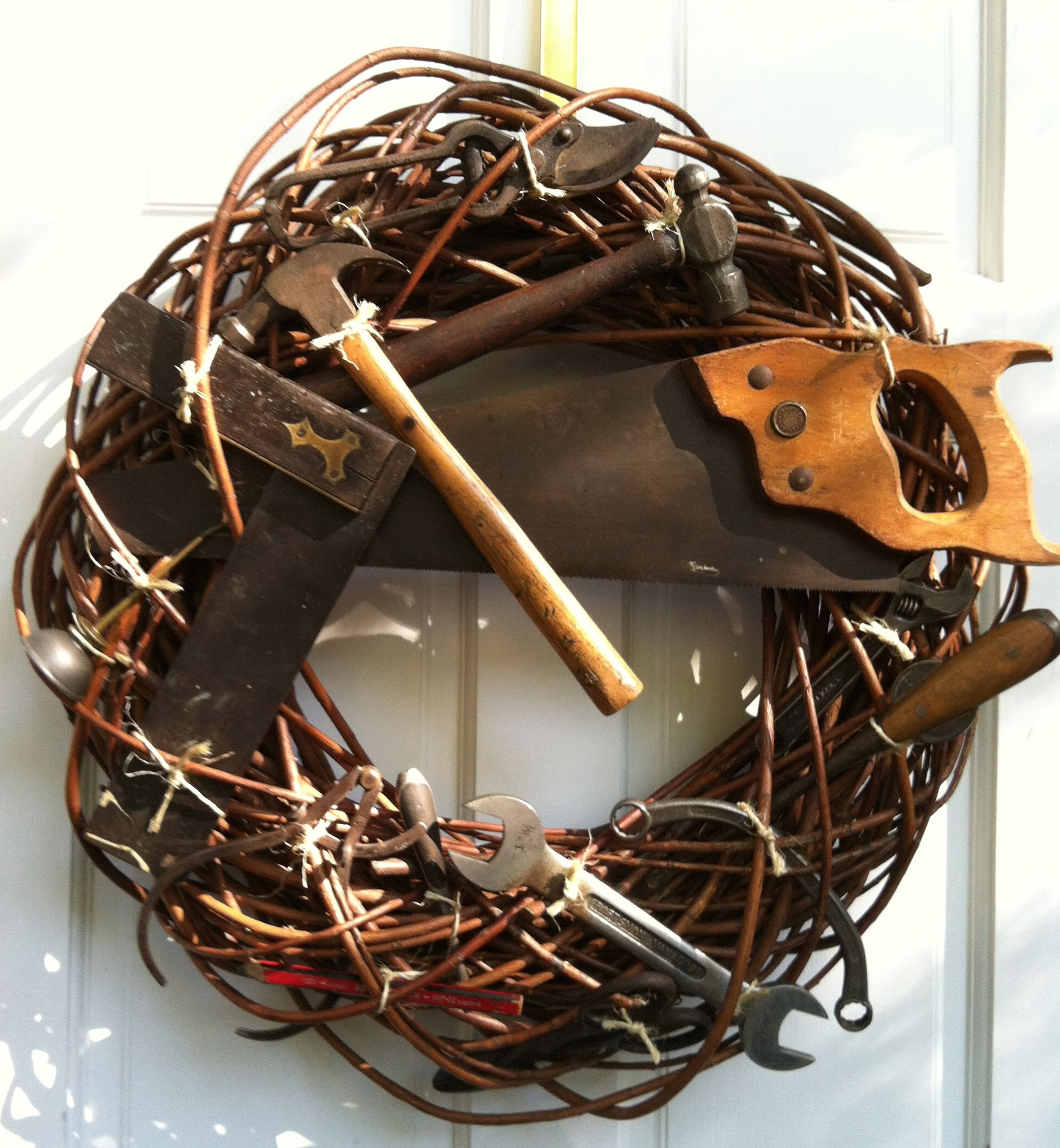 Grapevine wreath with old tools for my dad's door. Tools are tied on with binder's twine. Added magnets for leaving notes on the saw!