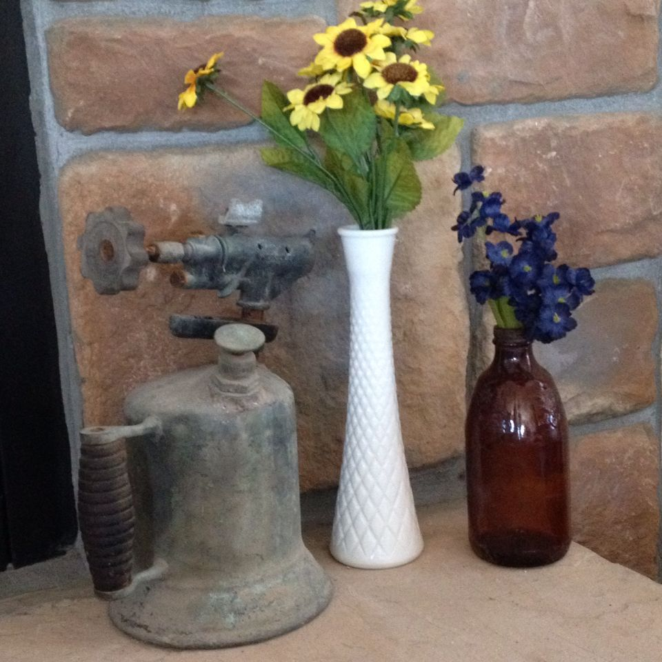 Old torch and glass bottle found in the creek for fireplace decor.