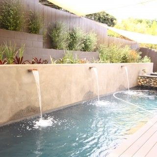 grey pebble lap pool with raised stone spa. the custom water