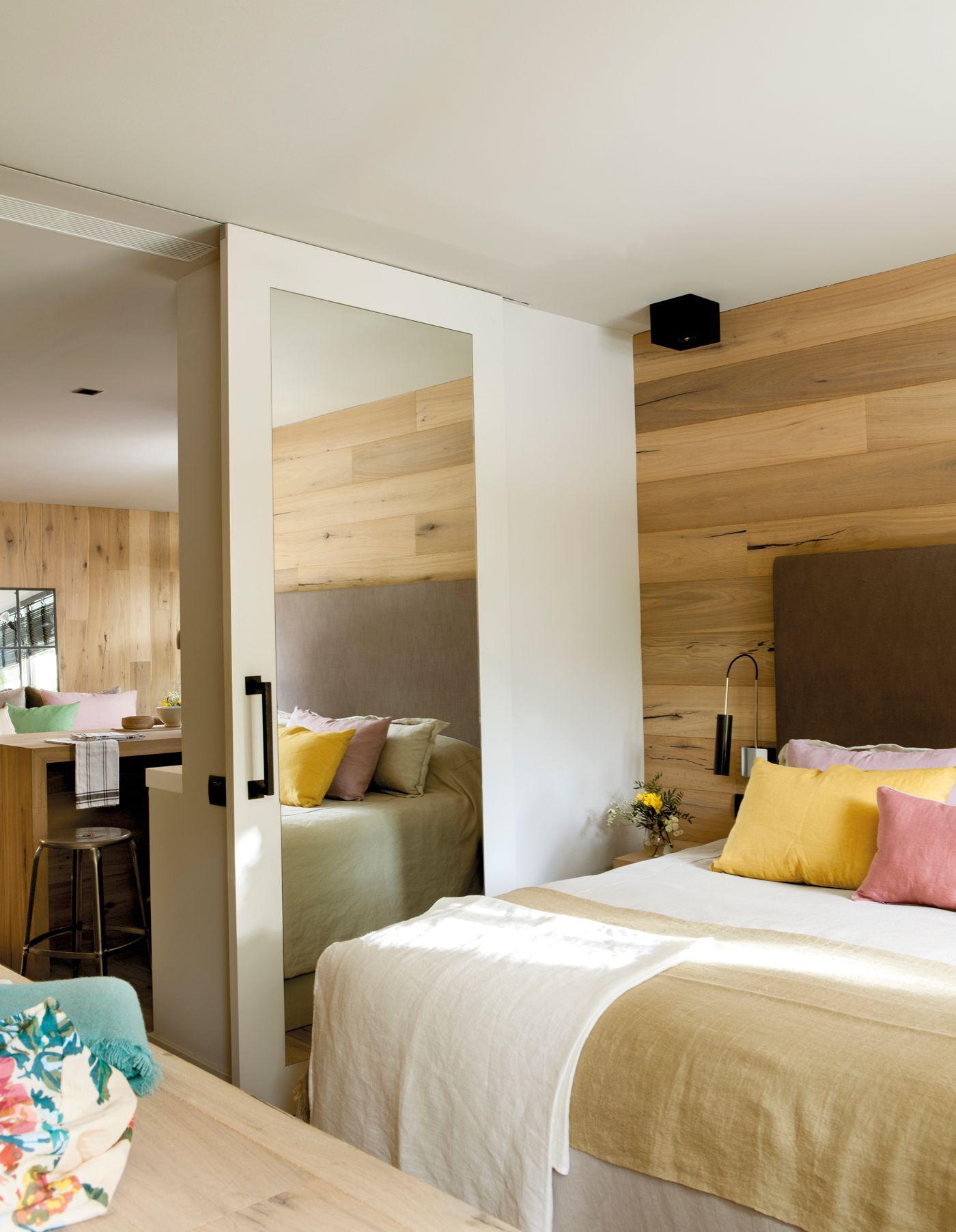 Dormitorio con puerta corredera con espejo y pared forrada de