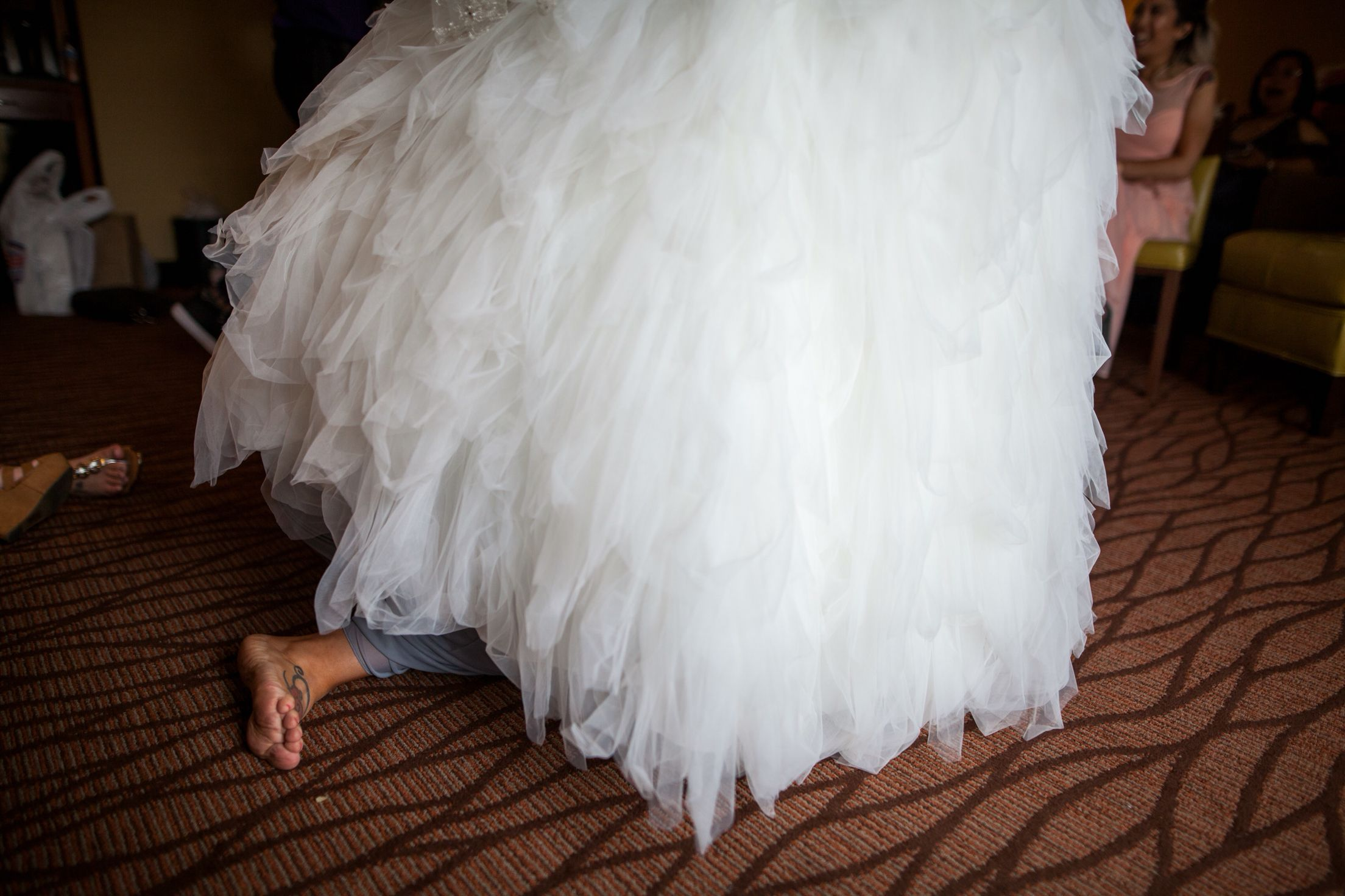 Maid of honor under brides gown to tie up corset strings