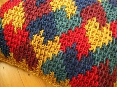 Front-of-Tunisian-Crochet-Cusion-with-hearts-in-red-burgundy-blue-green-and-curry-in-Alafoss-Lopi-by-Irene-Lundgaard-2.jpg 653×490 píxeles