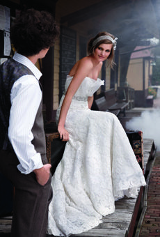Rivini's lavish lace-applique trumpet gown, featuring a sweetheart bodice with silk-organza folds and a crystal-beaded belt.    Dress, $7,940