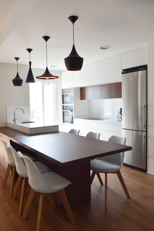 Blanca y luminosa cocina con península central y gran mesa de madera ...