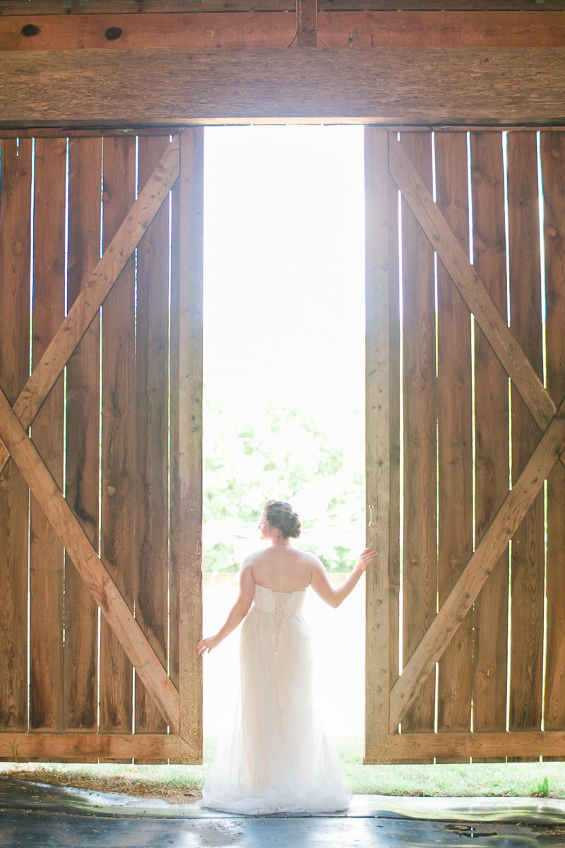 """""""A bride in a lace up dress from southern bride, inc in Yadkinville, NC poses for a portrait in Greensboro NC"""",  traditional farm wedding"""
