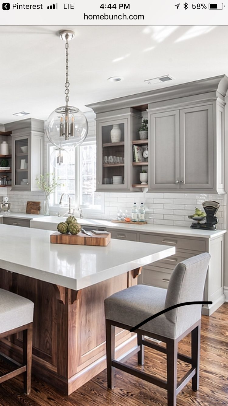 Gray cabinets with wood island and white countertop in kitchen