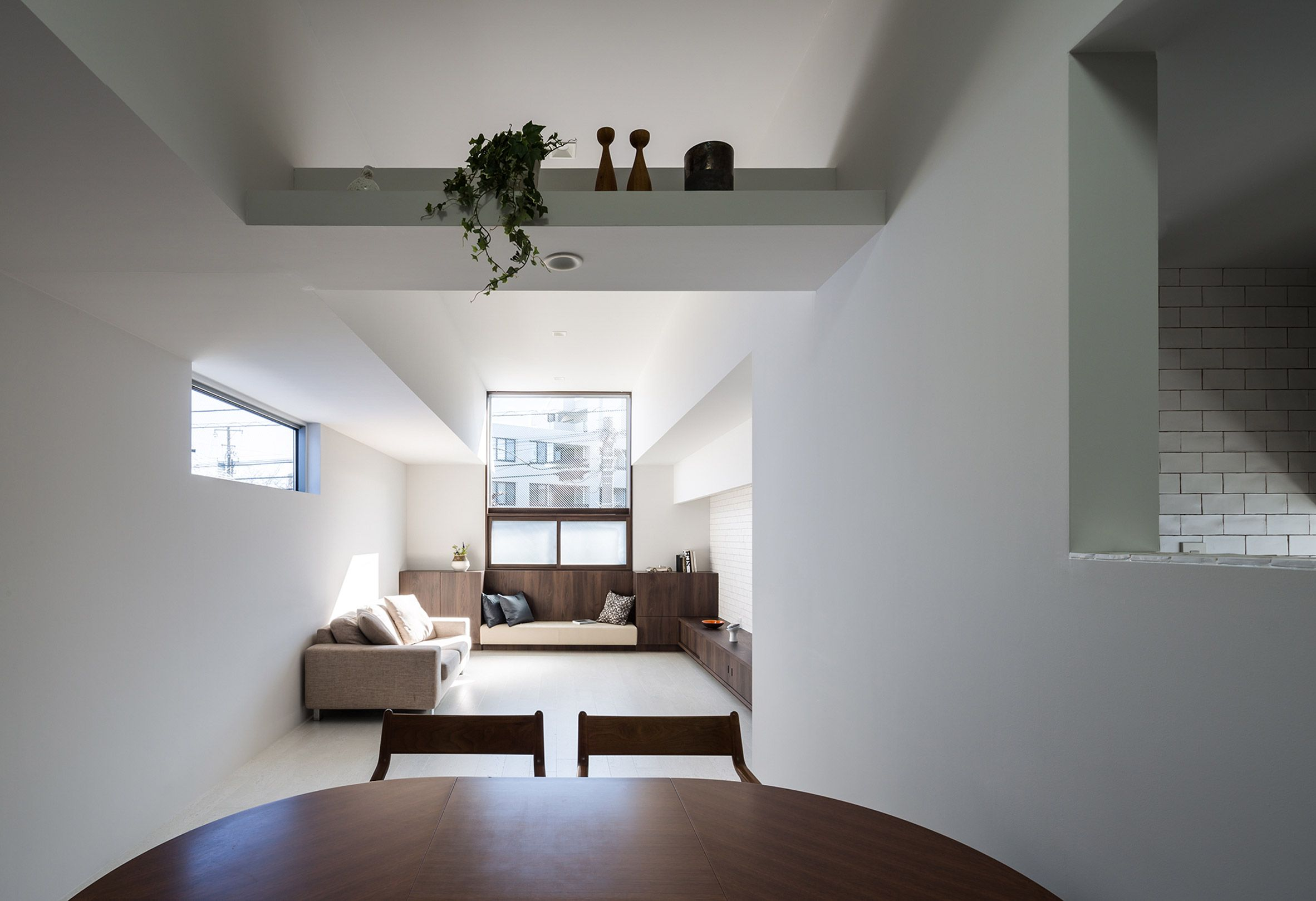 Bright white living spaces overhang gallery in topheavy tokyo house