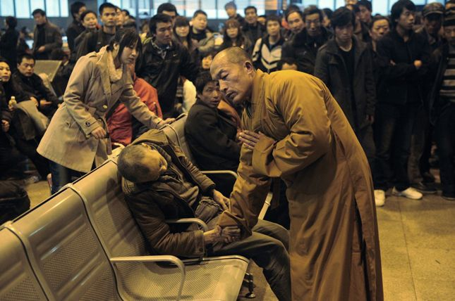 Un monaco prega per un uomo anziano morto improvvisamente in attesa di un treno in Shanxi Taiyuan, Cina.