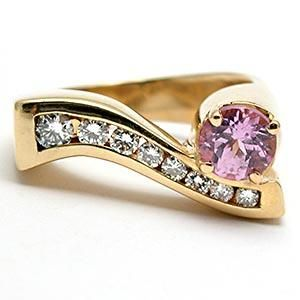 This well designed ring is crafted of solid 14k yellow gold and features a beautiful natural pink sapphire and is accented by a row of high quality channel set diamonds. This ring is previously owned buy in very good condition.