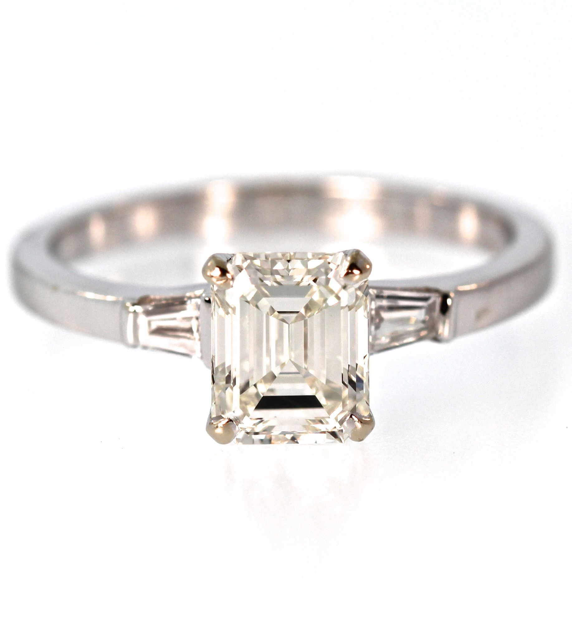 Set in a three stone 18k mounting with tapered baguettes is a