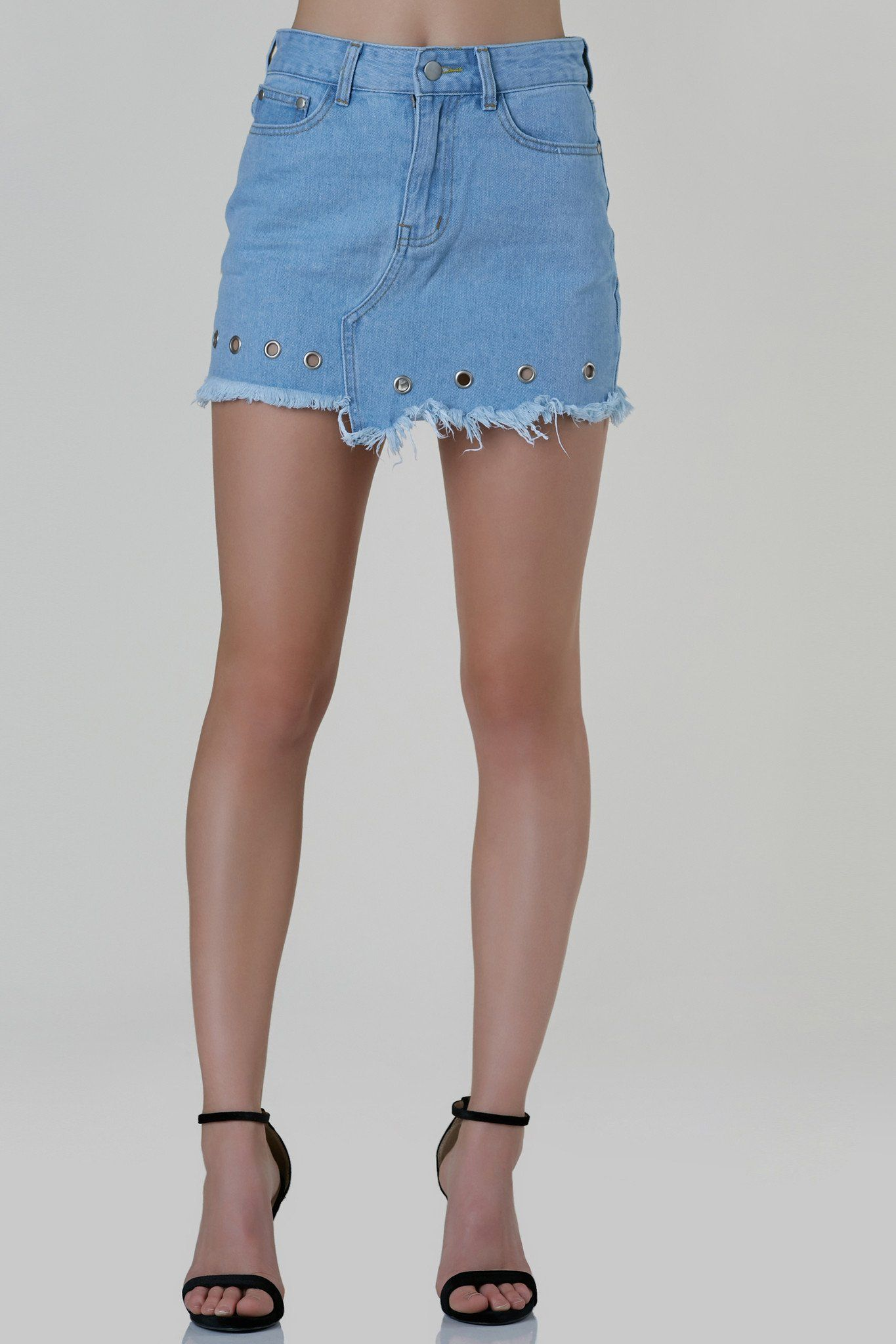 ccacc1c432 Trendy high rise denim skirt with frayed uneven raw hem finish. Silver  eyelet detailing in front with classic button zip closure.