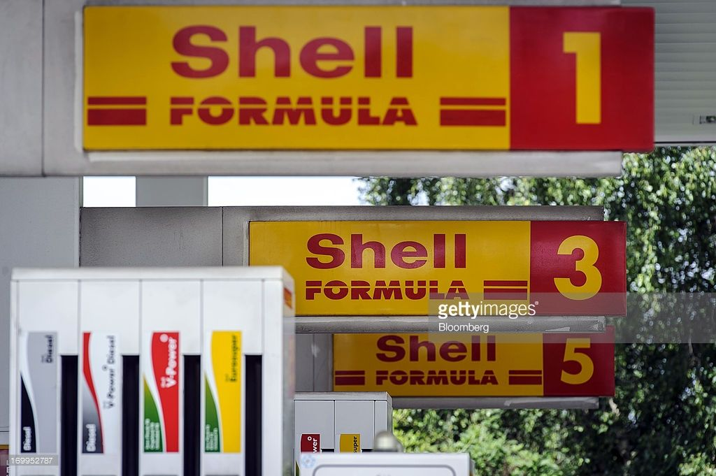 The Shell company logo sits on display above gas pumps at a fuel station, operated by Royal Dutch Shell Plc, in Brussels, Belgium, on Tuesday, June 4, 2013. Royal Dutch Shell Plc, BP Plc, Statoil ASA and Platts, the oil-price data collector owned by McGraw Hill Financial Inc., said they're being investigated after the European Commission conducted raids in three countries to ferret out evidence of collusion. Photographer: Jock Fistick/Bloomberg via Getty Images
