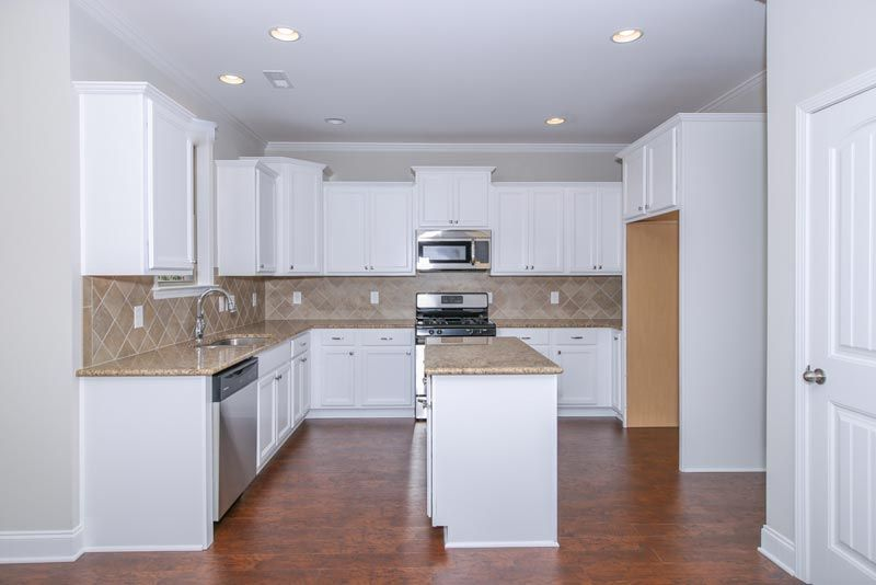 Kitchen with island, granite countertops, stainless steel appliances and tiered cabinets in the Nelson Craftsman KS