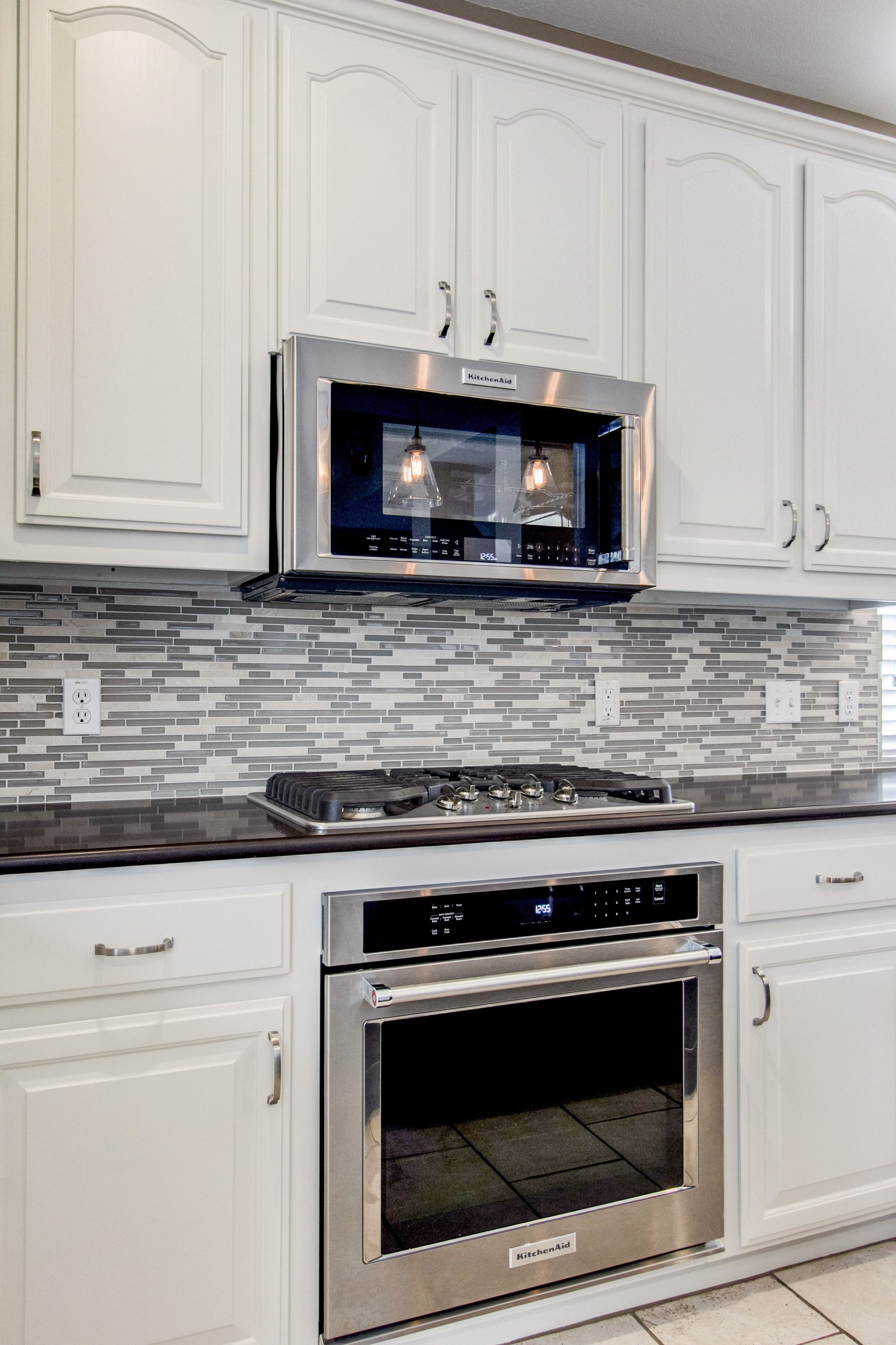 To update this kitchen we painted their existing stained cabinets antique white stained the island darker redid the backsplash with a glass stone mosaic