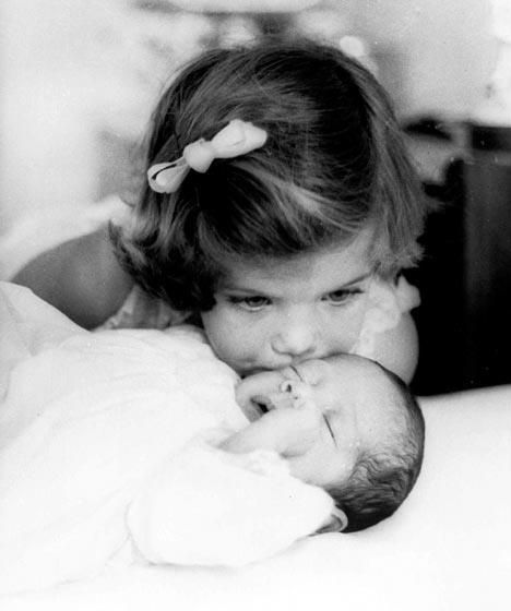 Caroline Kennedy aged 3, kissing her baby brother John F Kennedy Jr in 1961 in Palm Beach, Florida