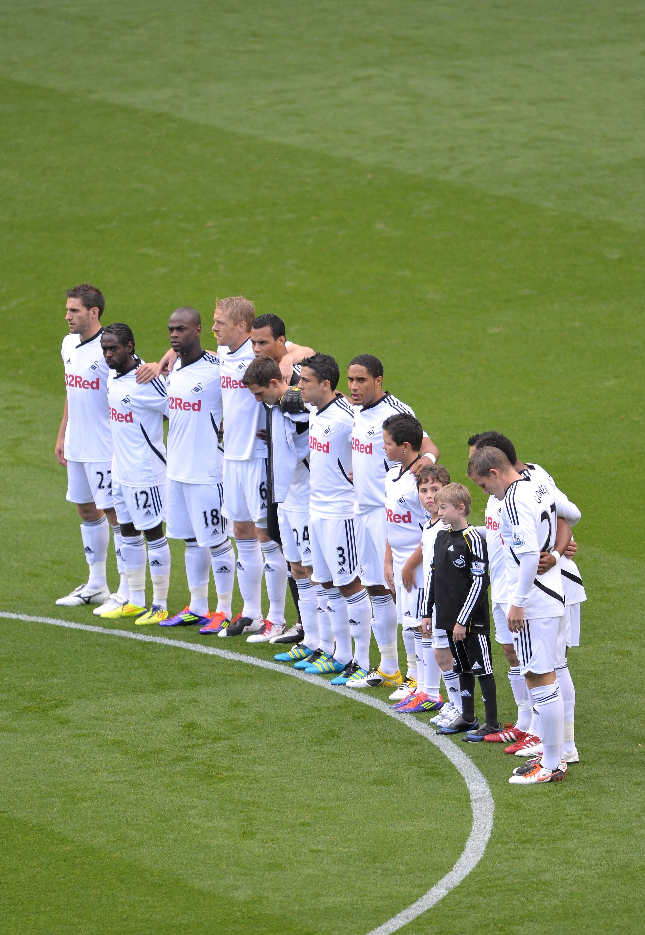 (12) The day after the bodies of the four miners are recovered, Swansea City players pay their respects with a minute's silence.