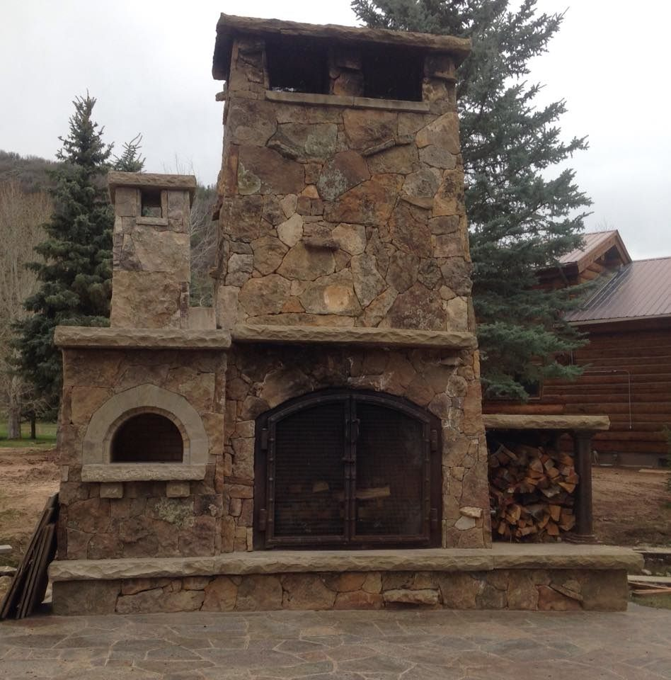 a beautifully crafted outdoor fireplace with natural stone veneer