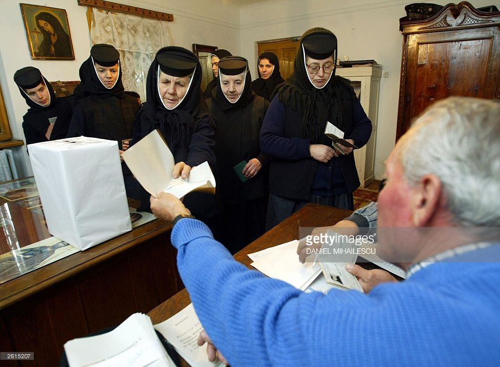 A member of the voting commission gives the vote bulletin to a nun at the Pasarea nunnery on the second day of the national referendum for a new constitution in Branesti village, near Bucharest 19 October 2003 . Almost 200 nuns vote for the new constitution at the Pasarea nunnery.