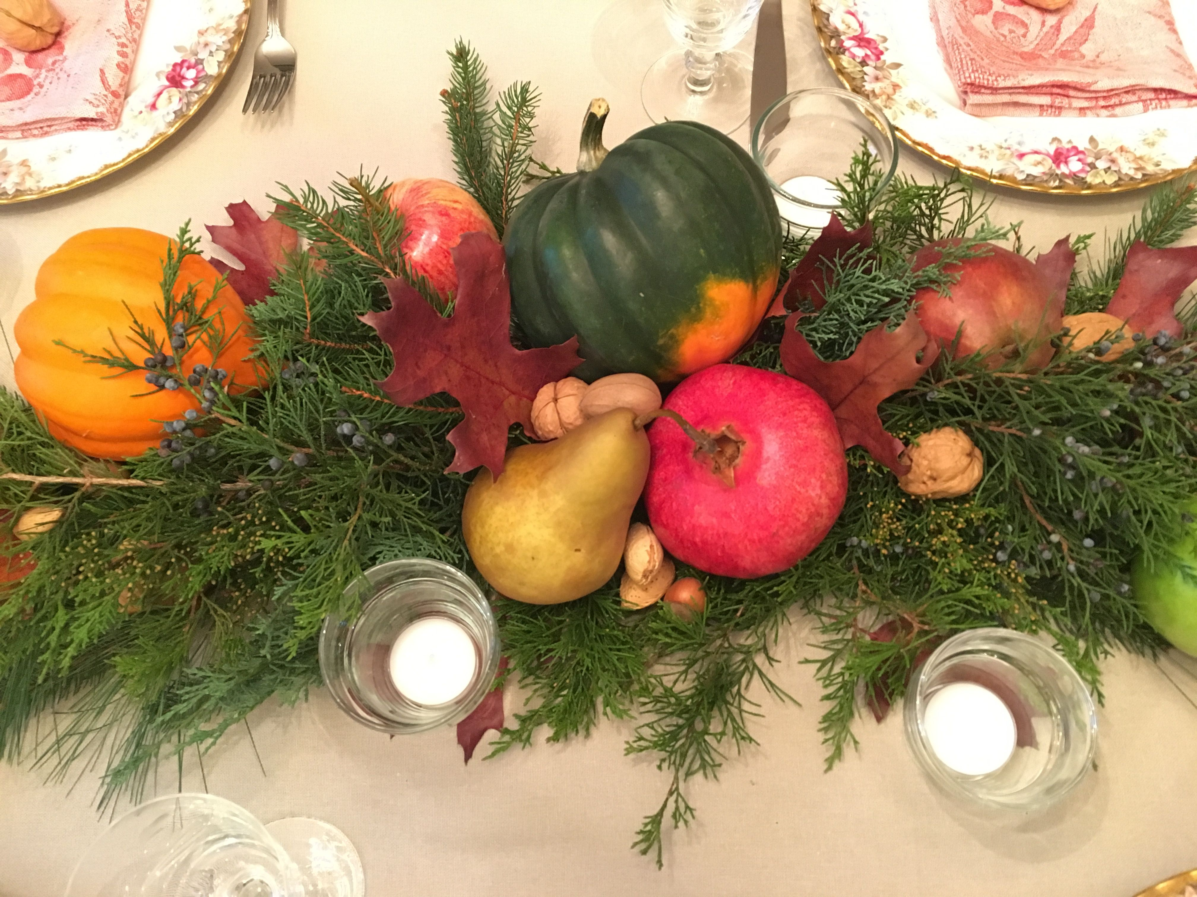 Thanksgiving table. Harvest centerpiece with fruit, squash ...